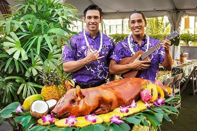 Men standing behind roast pig at luau
